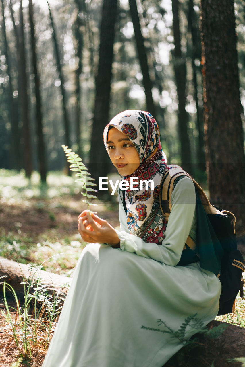 MIDSECTION OF WOMAN HOLDING TREE IN FOREST
