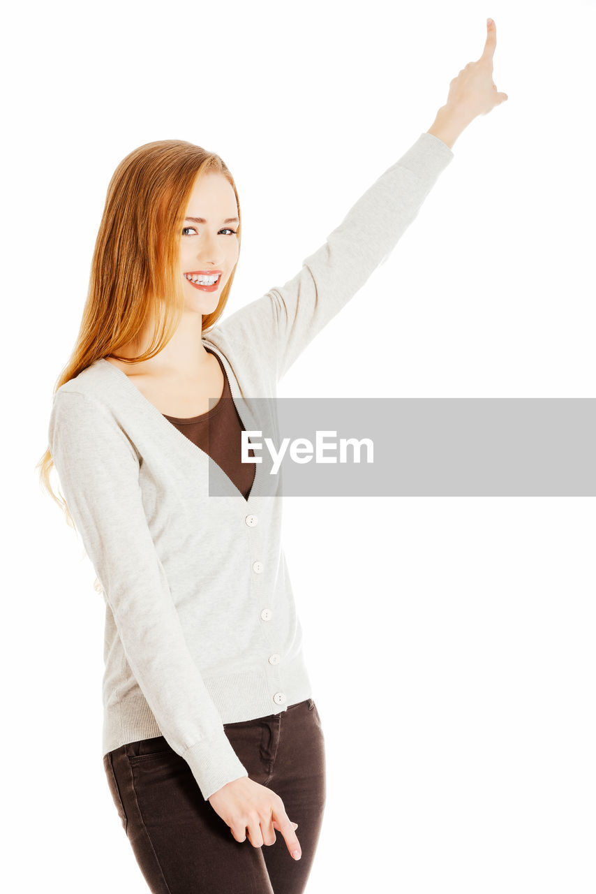 Portrait of smiling young woman pointing against white background