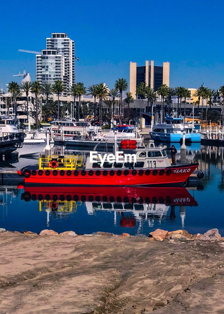 nautical vessel, moored, building exterior, architecture, transportation, mode of transport, harbor, built structure, marina, outdoors, clear sky, sea, water, no people, blue, travel destinations, day, city, cityscape, sky, nature, sailing, yacht, tree