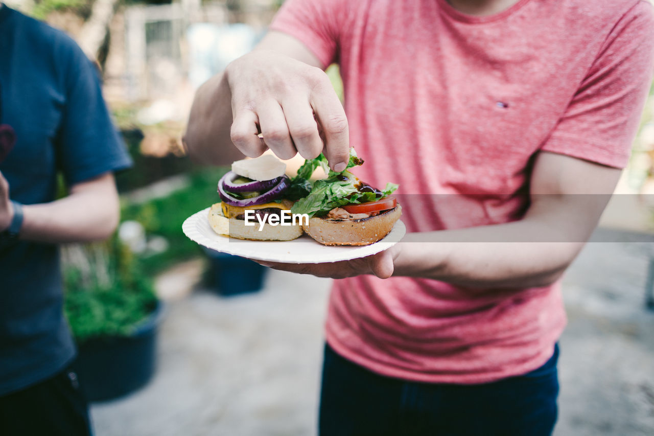 Midsection Of Man Holding Burger In Plate