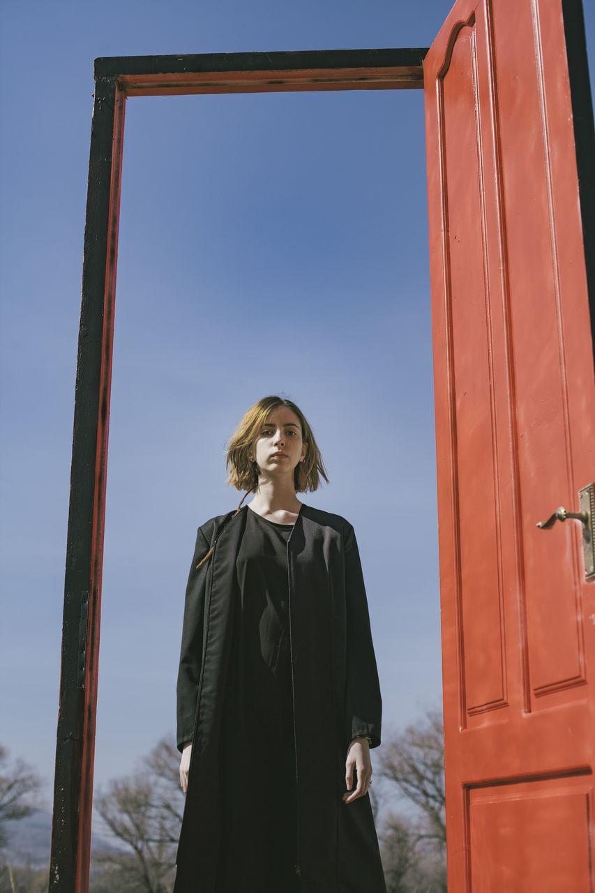 Portrait of woman standing at door against sky