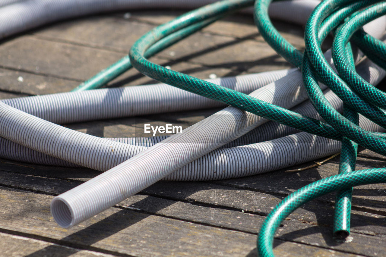 connection, close-up, rope, cable, no people, technology, tangled, still life, day, complexity, green color, equipment, tied up, outdoors, electricity, blue, table, metal, string, garden hose