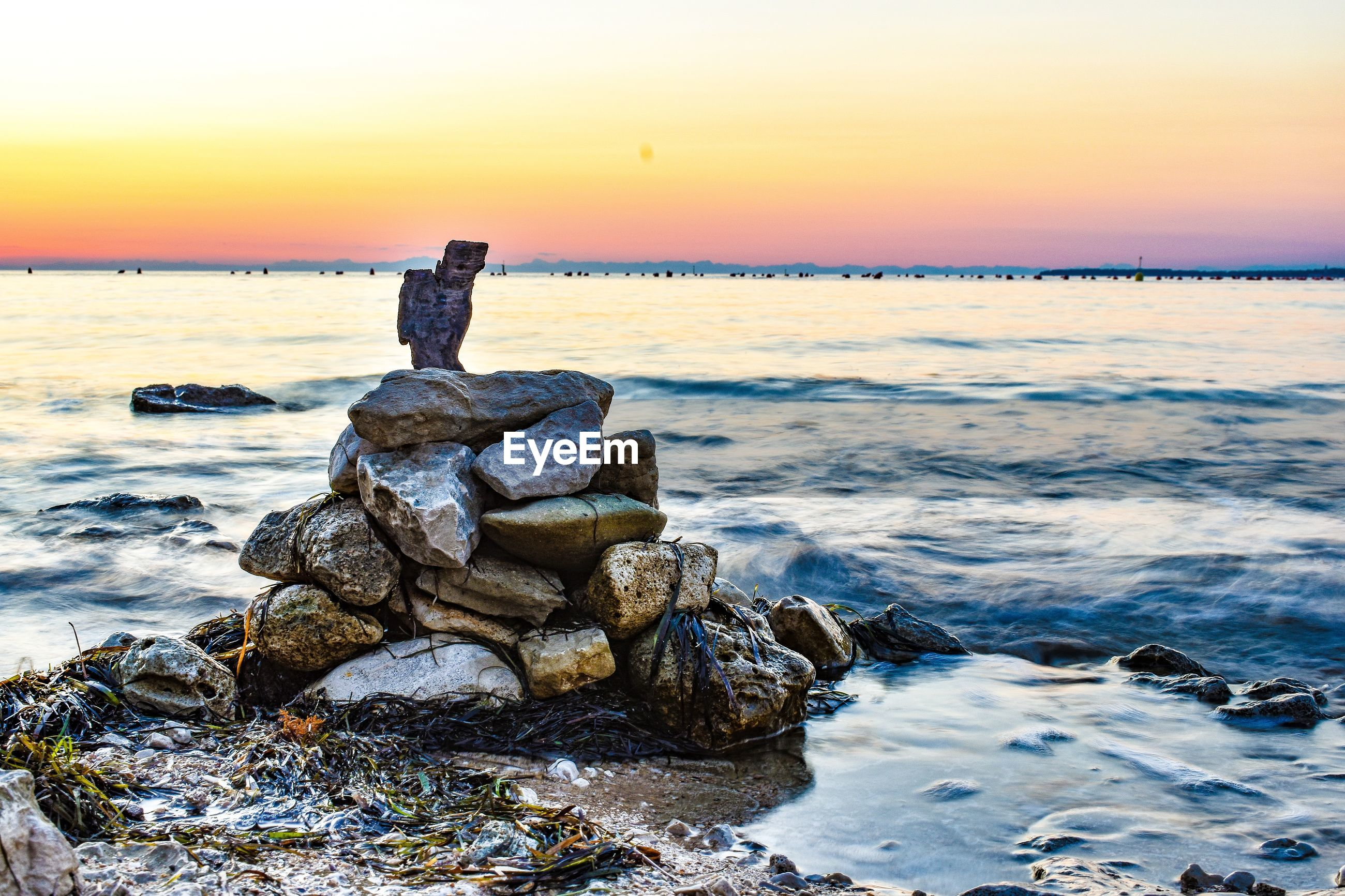 SCENIC VIEW OF ROCKS AT BEACH DURING SUNSET