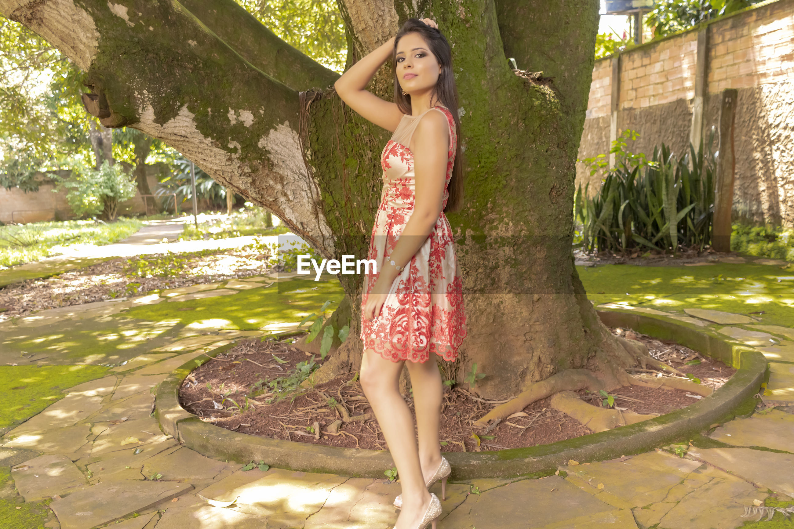 Portrait of beautiful woman standing against tree trunk
