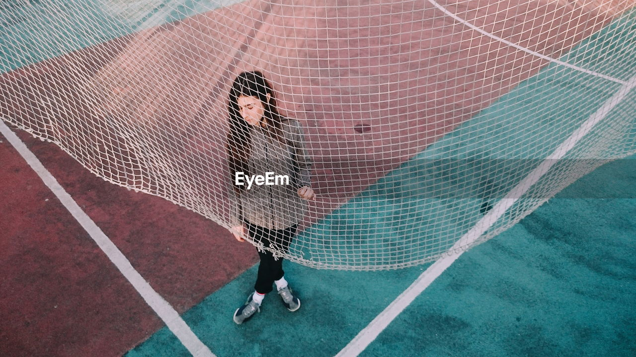 High Angle View Of Woman Standing By Net On Playing Field