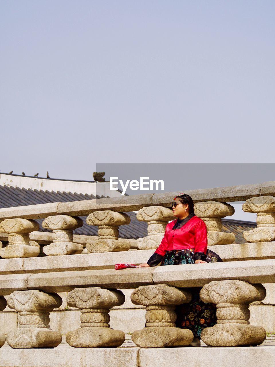 WOMAN SITTING AGAINST BUILT STRUCTURE