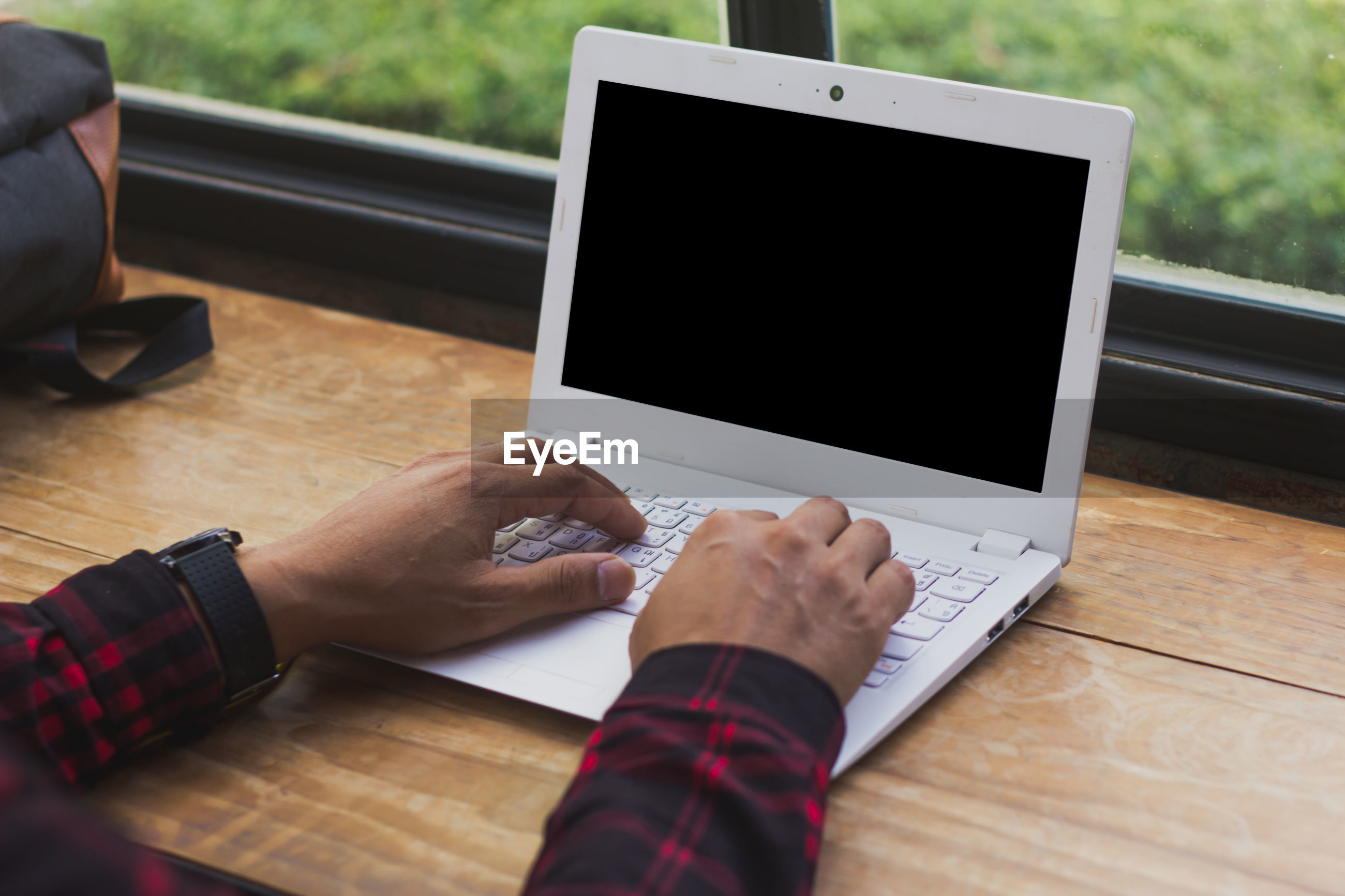 Cropped hands using laptop in cafe