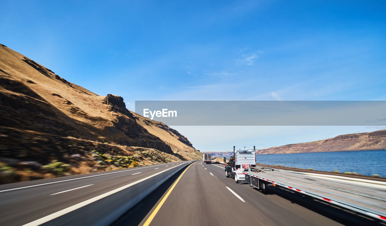 transportation, road, mode of transportation, sky, land vehicle, motor vehicle, car, mountain, symbol, road marking, marking, the way forward, nature, direction, day, sign, motion, no people, cloud - sky, on the move, diminishing perspective, outdoors, dividing line
