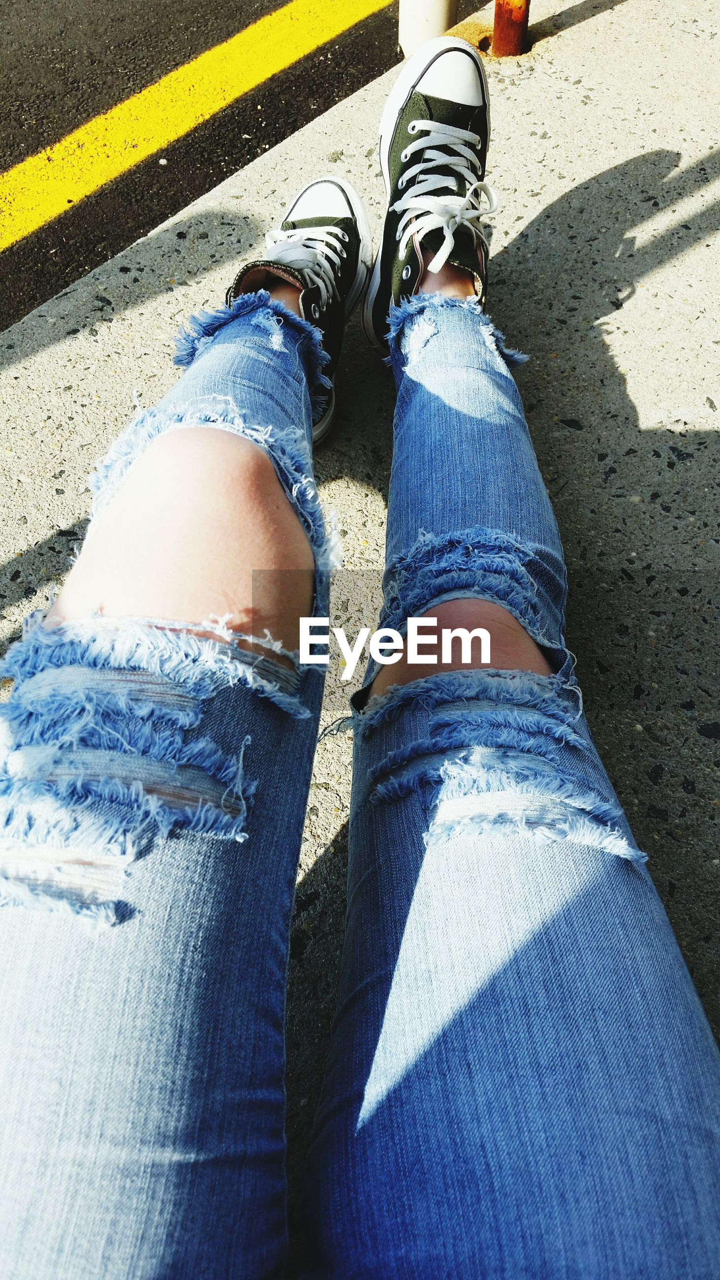 low section, person, shoe, lifestyles, jeans, standing, human foot, personal perspective, footwear, leisure activity, high angle view, casual clothing, men, street, canvas shoe, denim