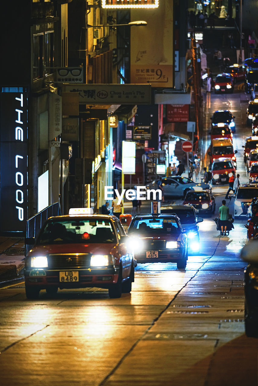 mode of transportation, car, motor vehicle, city, transportation, illuminated, night, land vehicle, street, architecture, city life, building exterior, city street, built structure, text, road, communication, sign, incidental people, taxi
