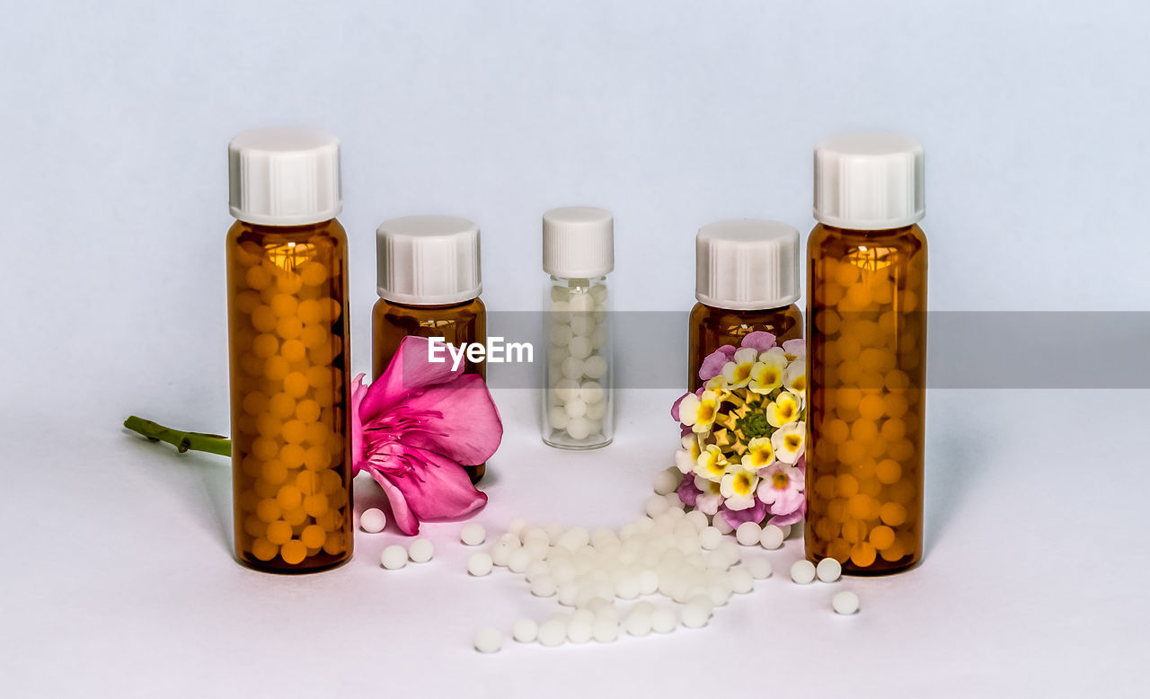 Close-up of flower and medicine against white background