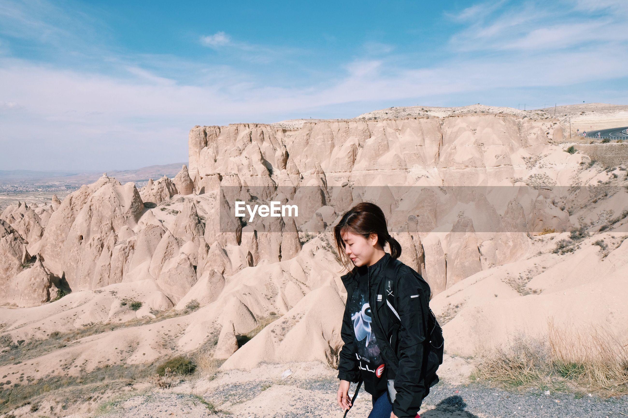 Woman walking against rock formation in desert