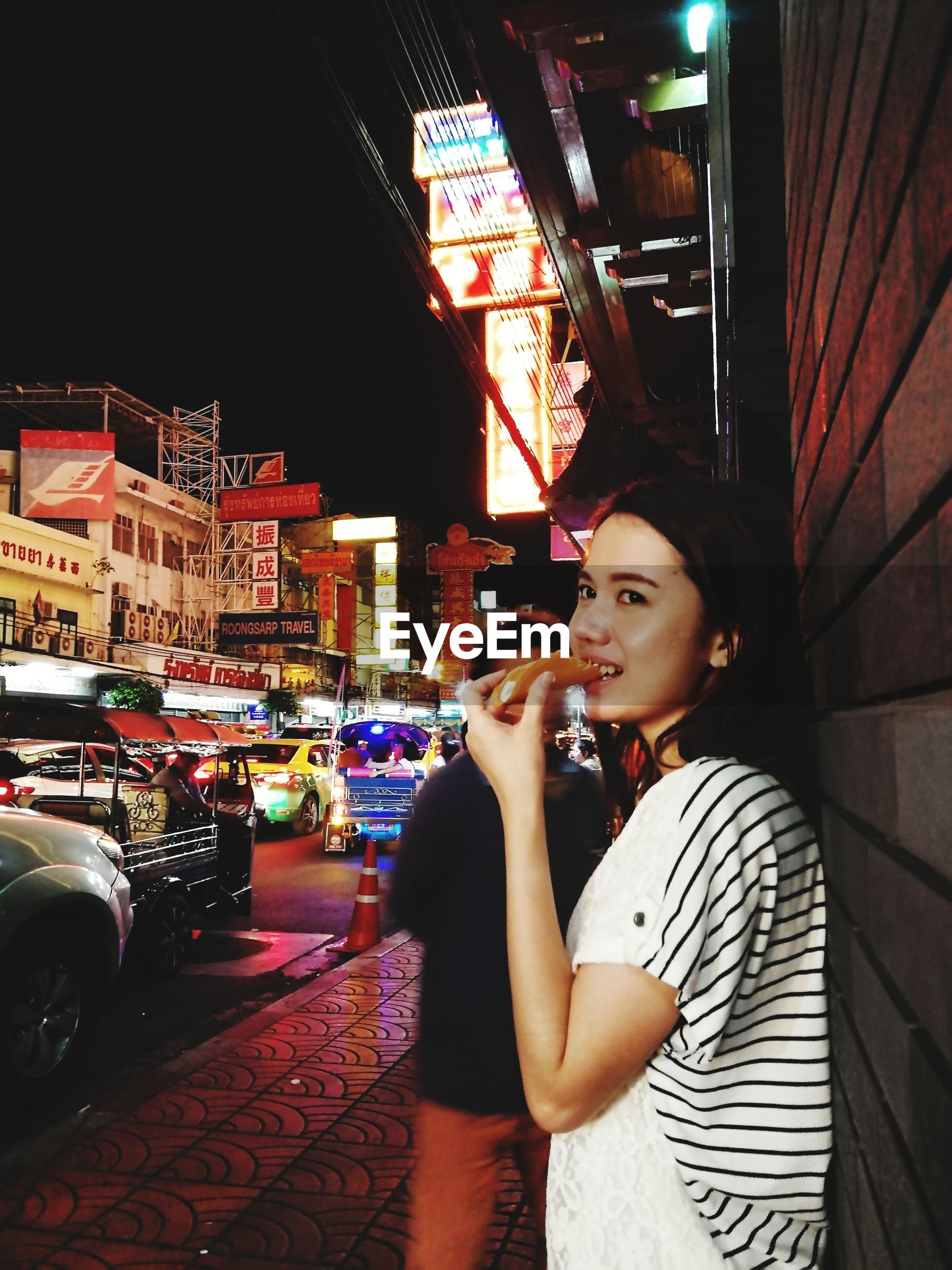 Young woman eating while standing on footpath in city at night