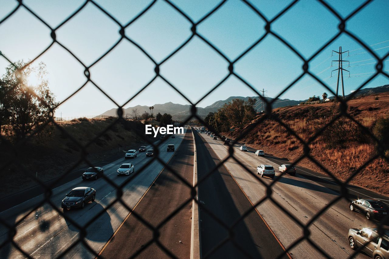 Cars Moving On Highway Seen Through Chainlink Fence Against Clear Sky