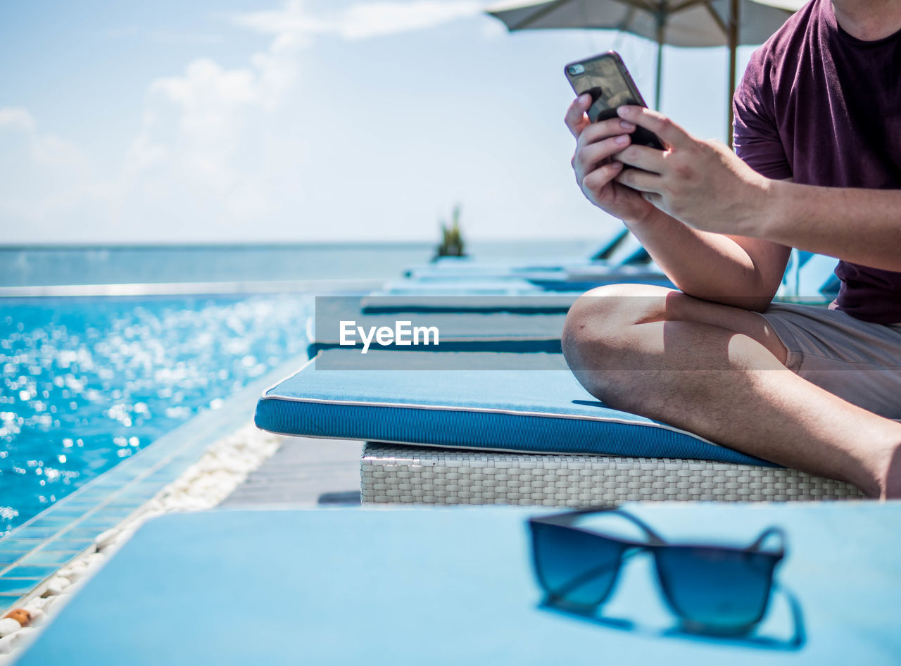 Midsection of man using smart phone while sitting by swimming pool