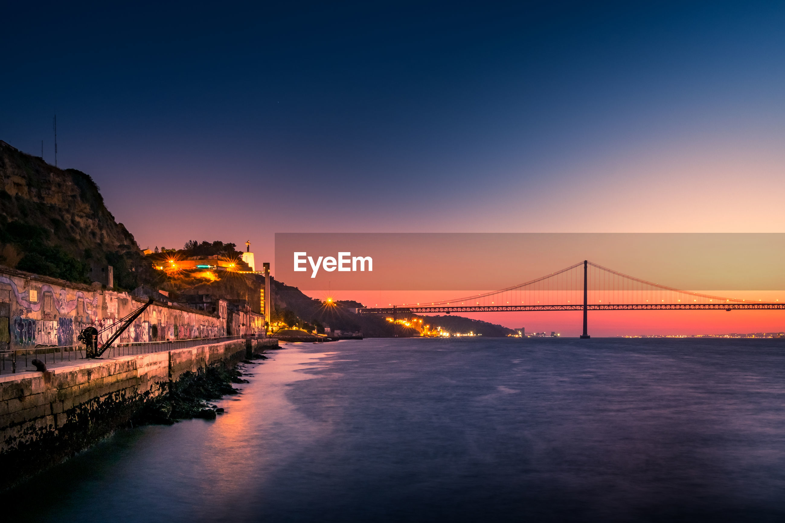Bridge over sea against sky at sunset