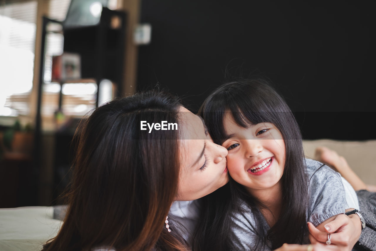 Mother kissing on cheek of cute daughter at home