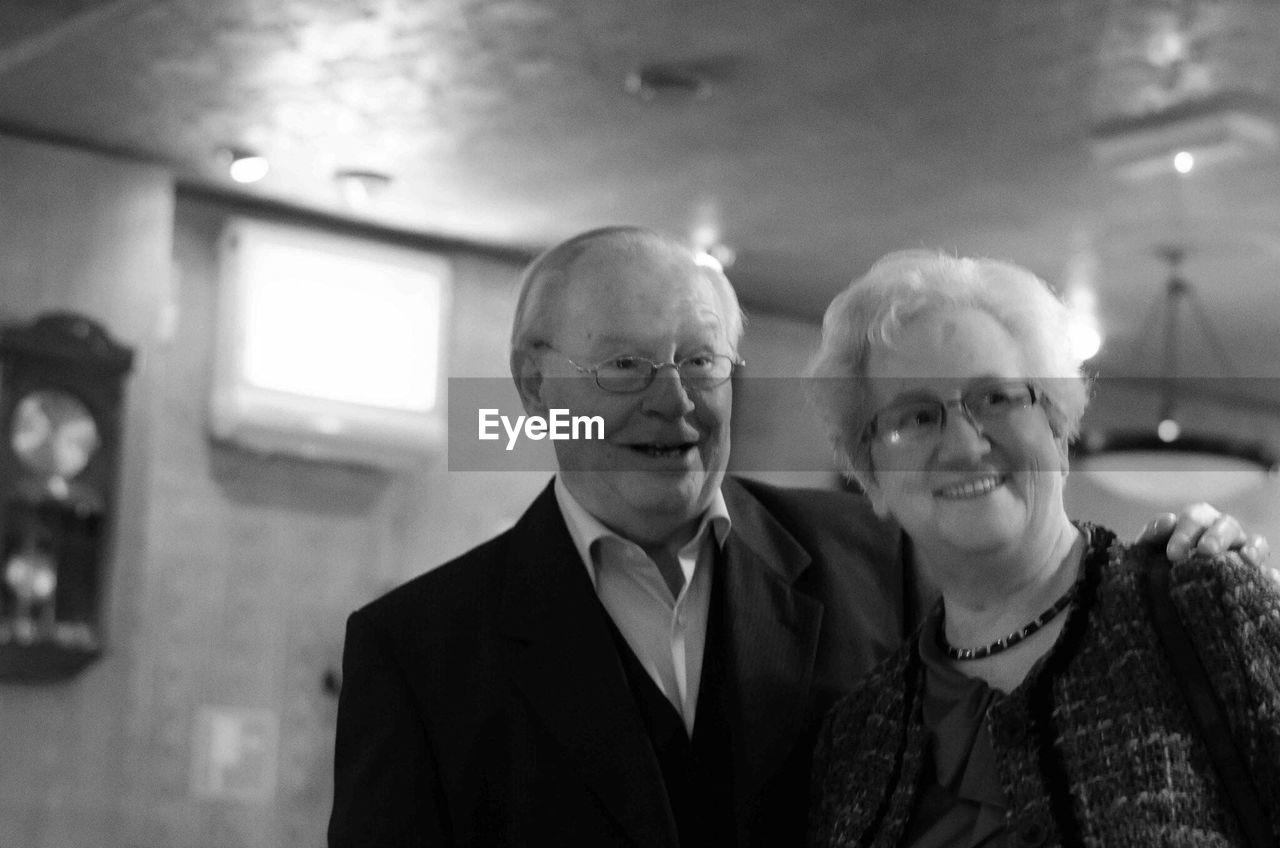 Smiling Senior Couple At Illuminated Room