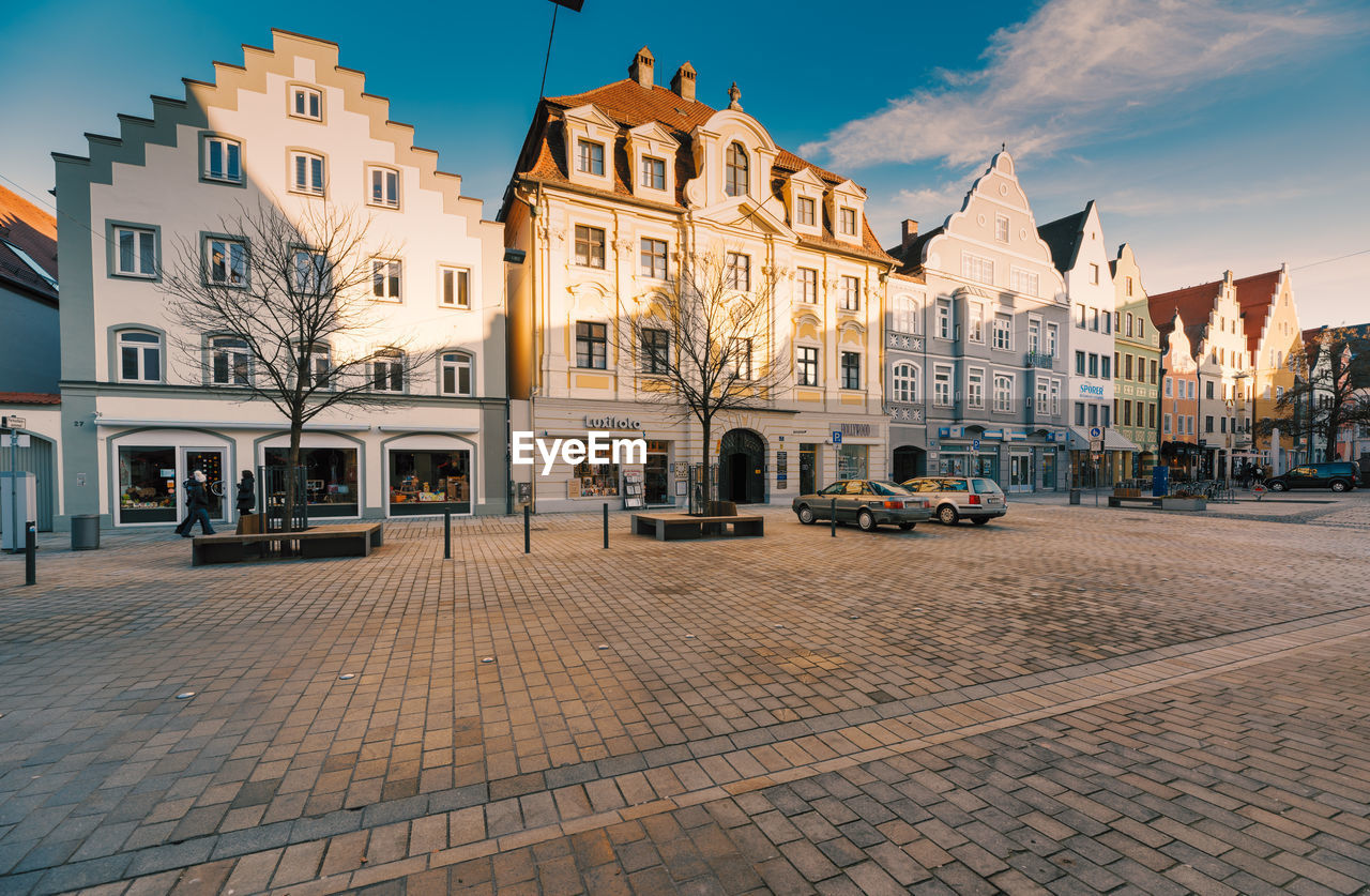 building exterior, built structure, architecture, city, building, street, motor vehicle, sky, car, mode of transportation, transportation, nature, residential district, land vehicle, cobblestone, incidental people, cloud - sky, day, footpath, town, paving stone, outdoors