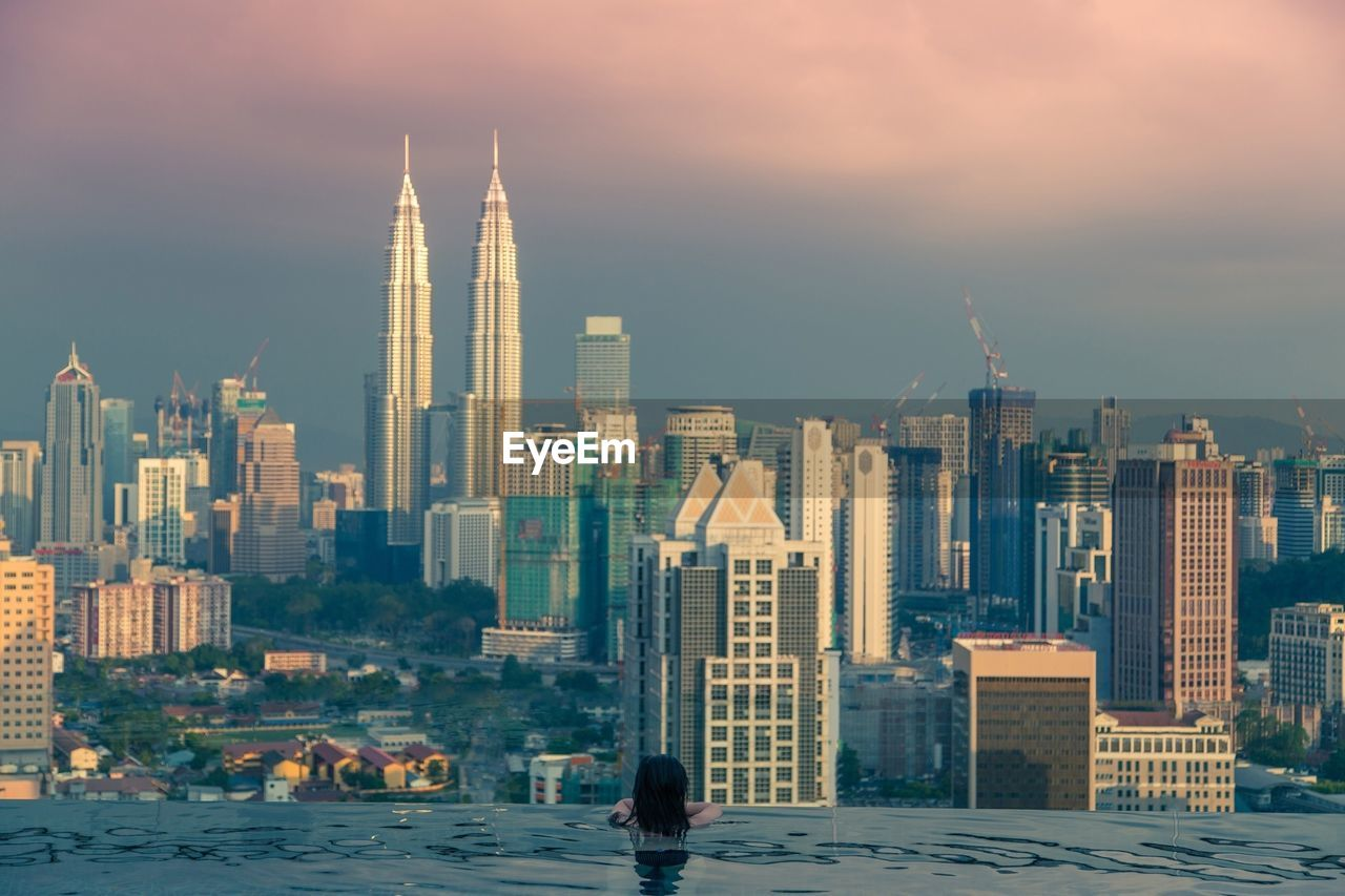 Rear View Of Woman In Marina Bay Sands Swimming Pool Looking At Petronas Towers During Sunset