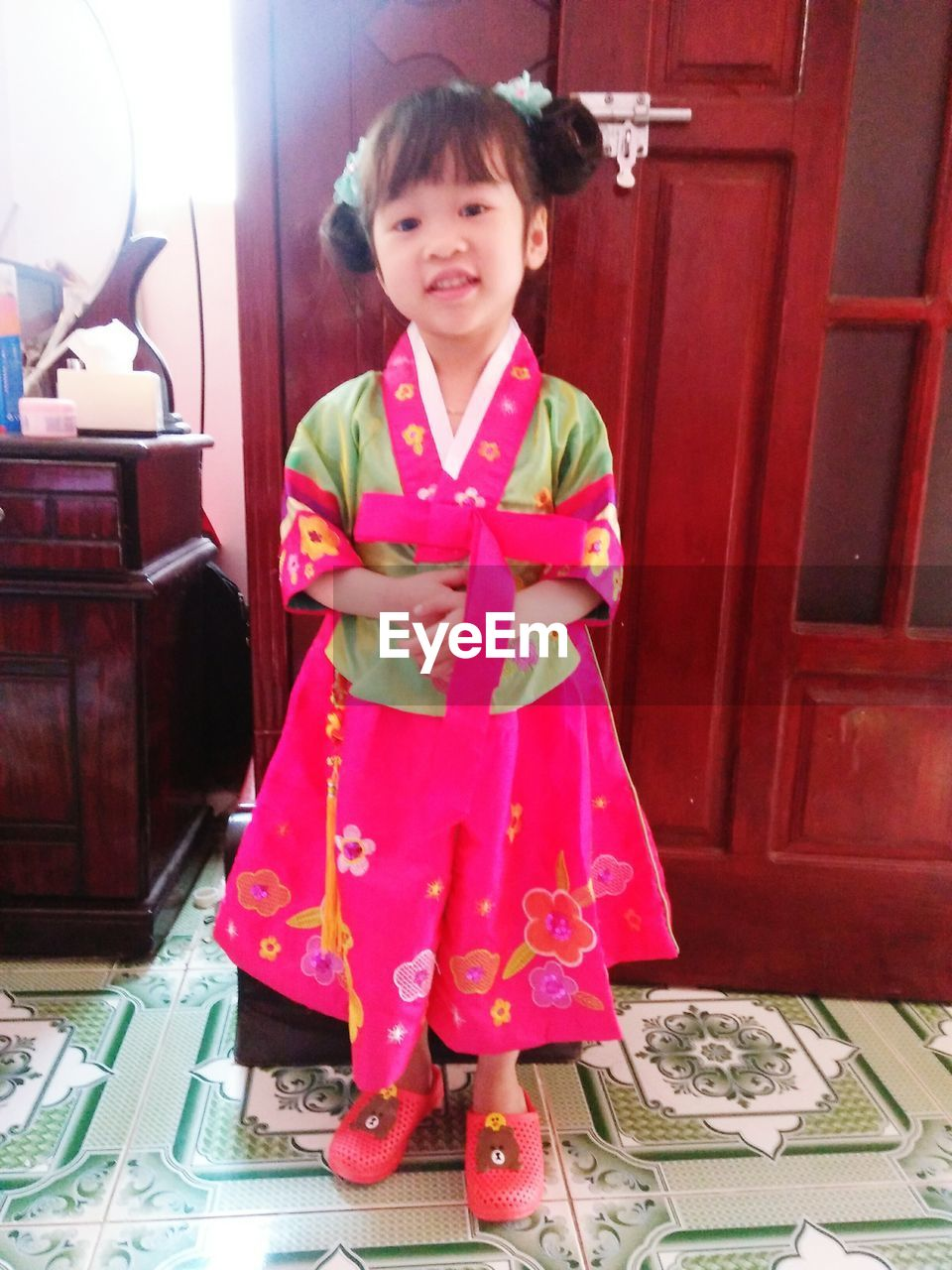 Portrait of smiling cute girl wearing dress at home