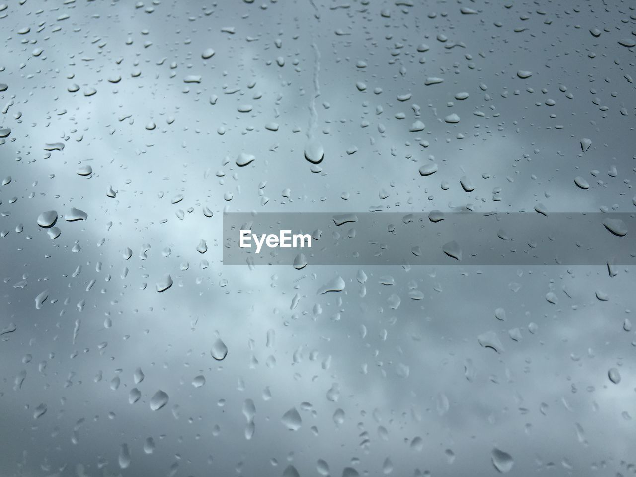 Close-Up Of Waterdrops On Glass Against Blurred Background