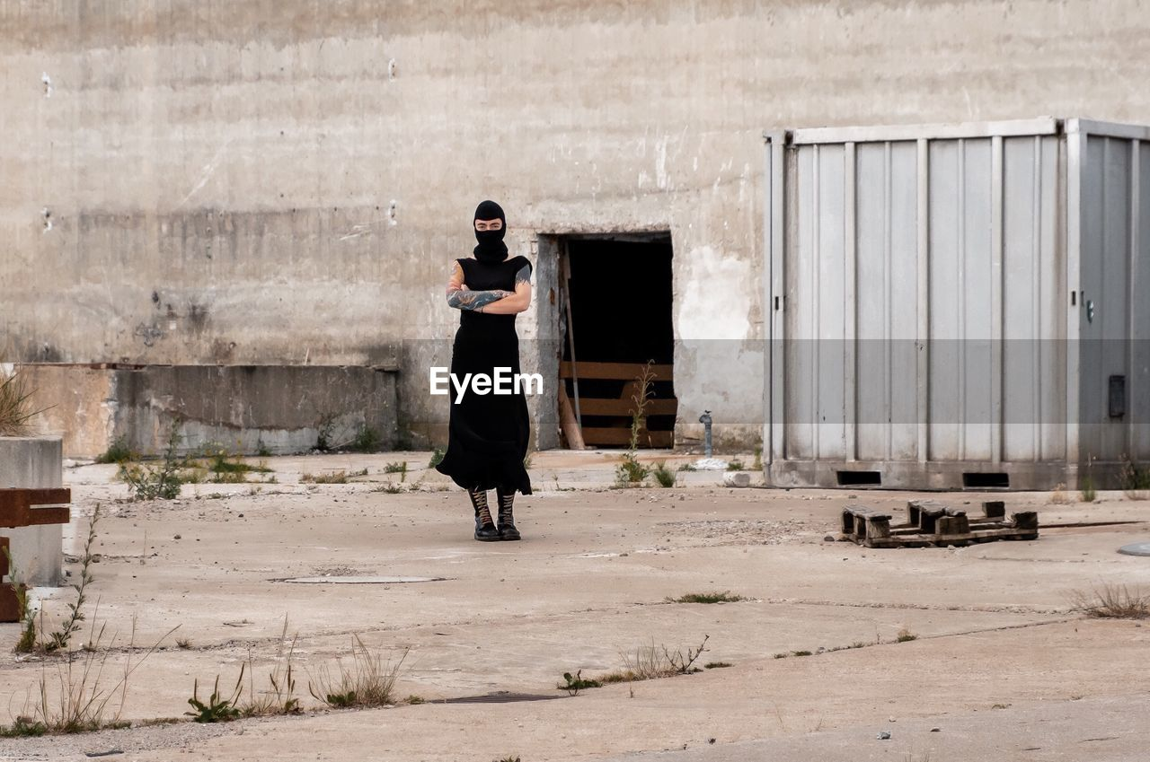 Portrait Of Woman In Costume Standing Against Old Factory