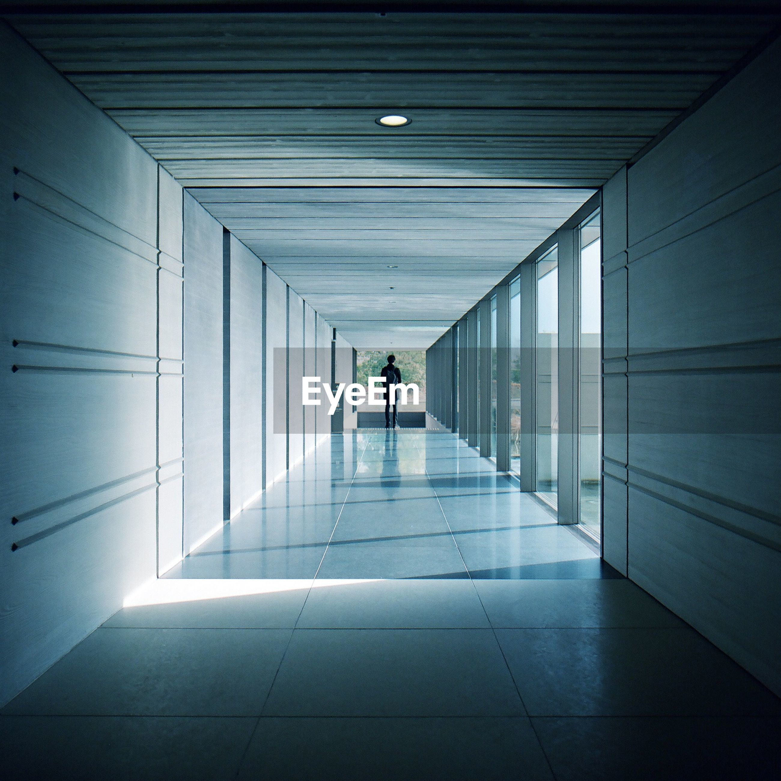 Distant view of man standing at end of corridor in building