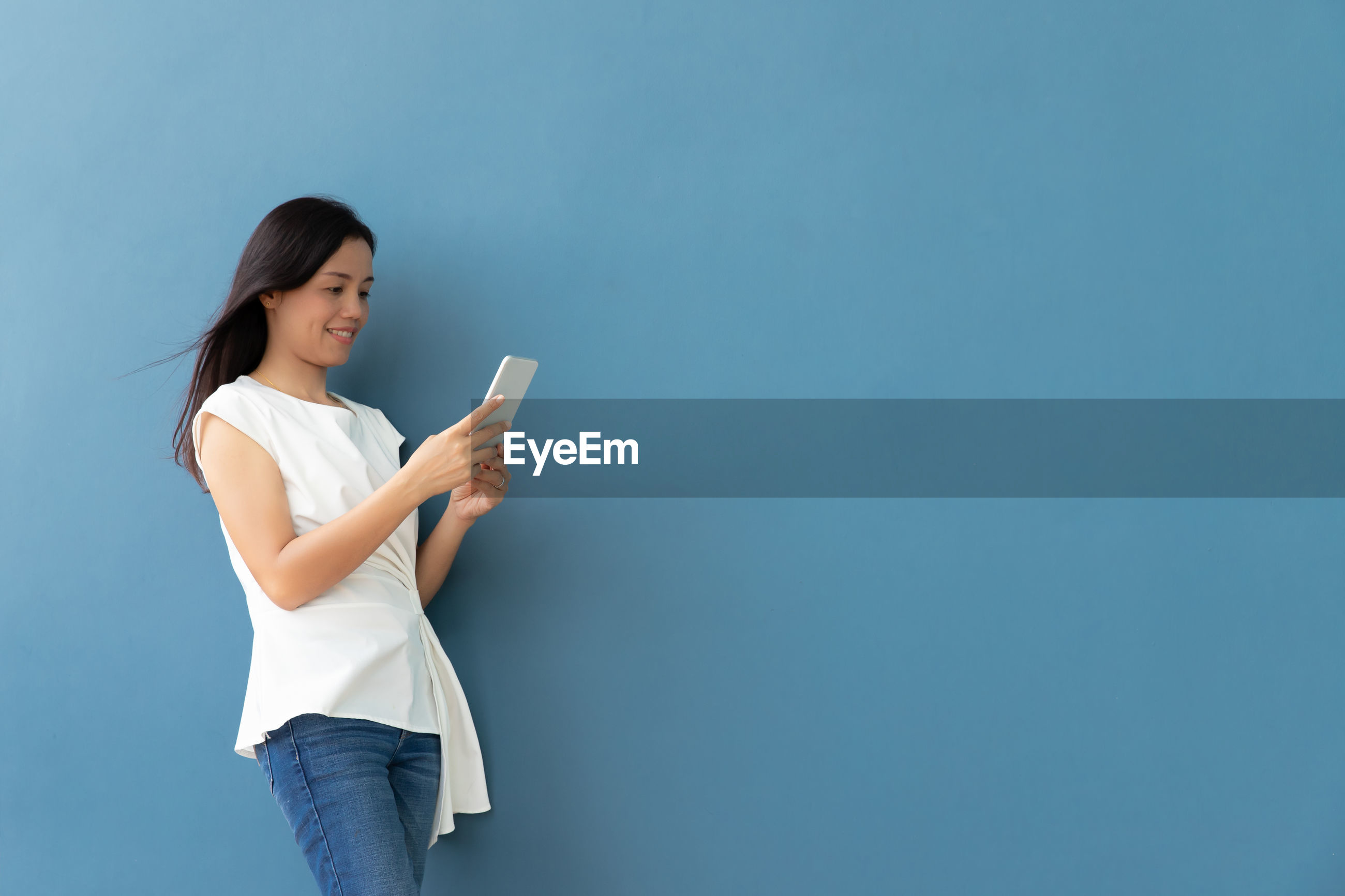 Woman using smart phone while standing against blue wall