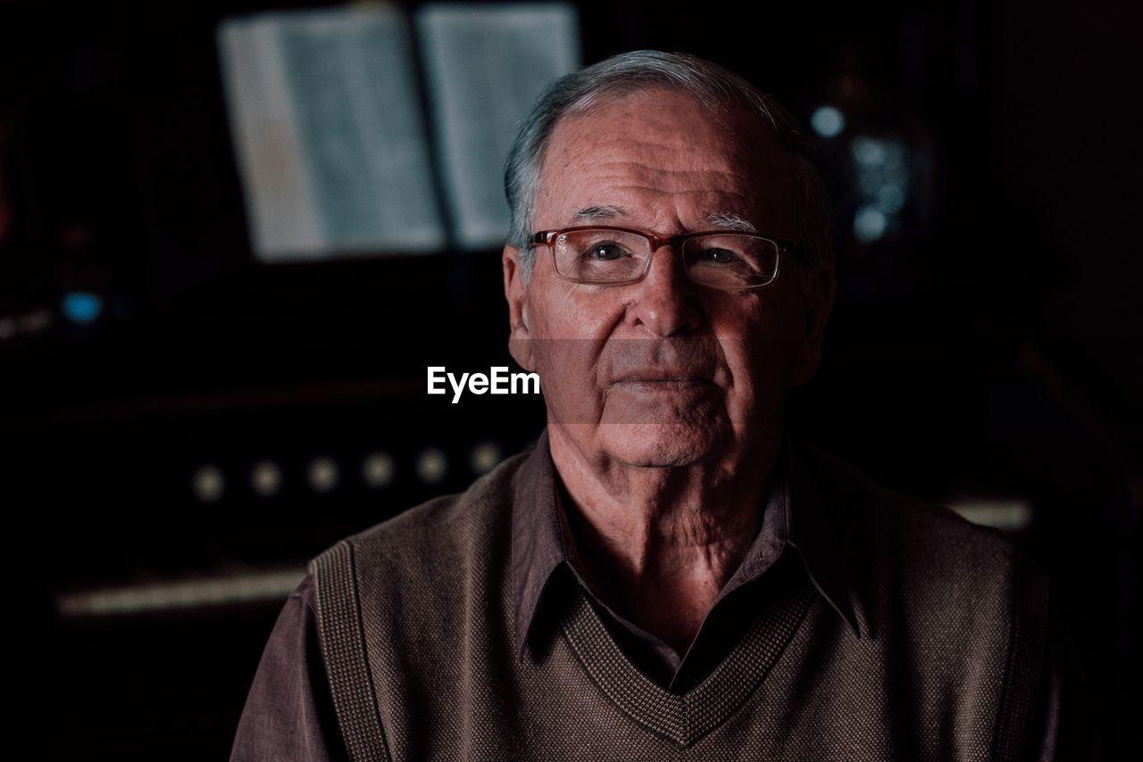 Portrait Of Senior Man Wearing Eyeglasses In Darkroom