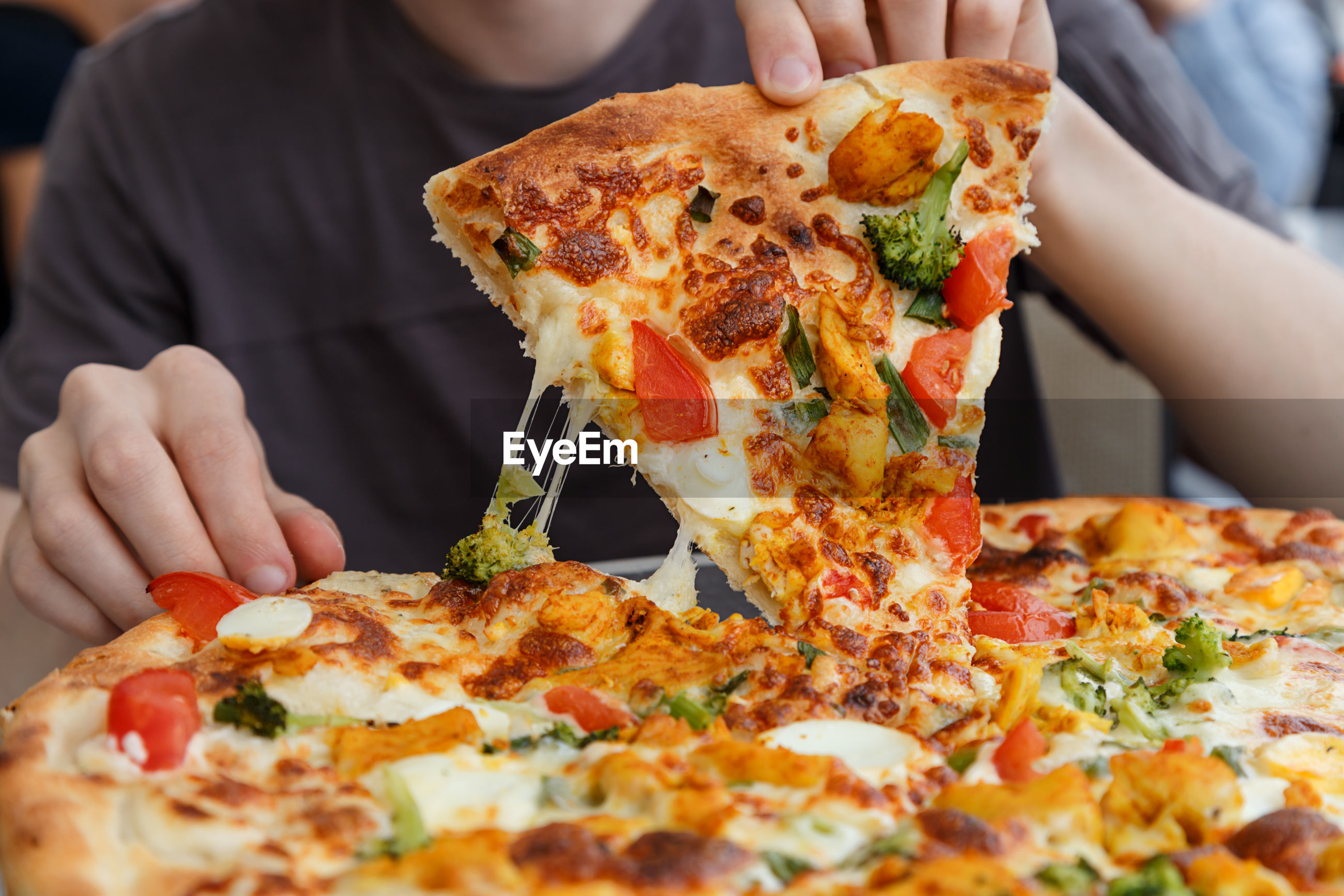 Midsection of man with pizza at table