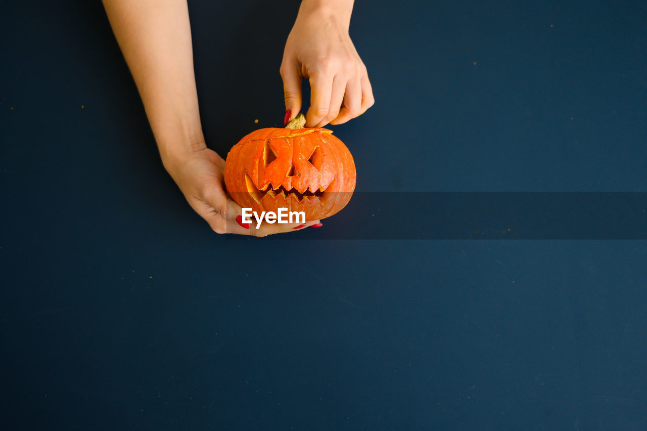 Low angle view of hand holding pumpkin against blue background