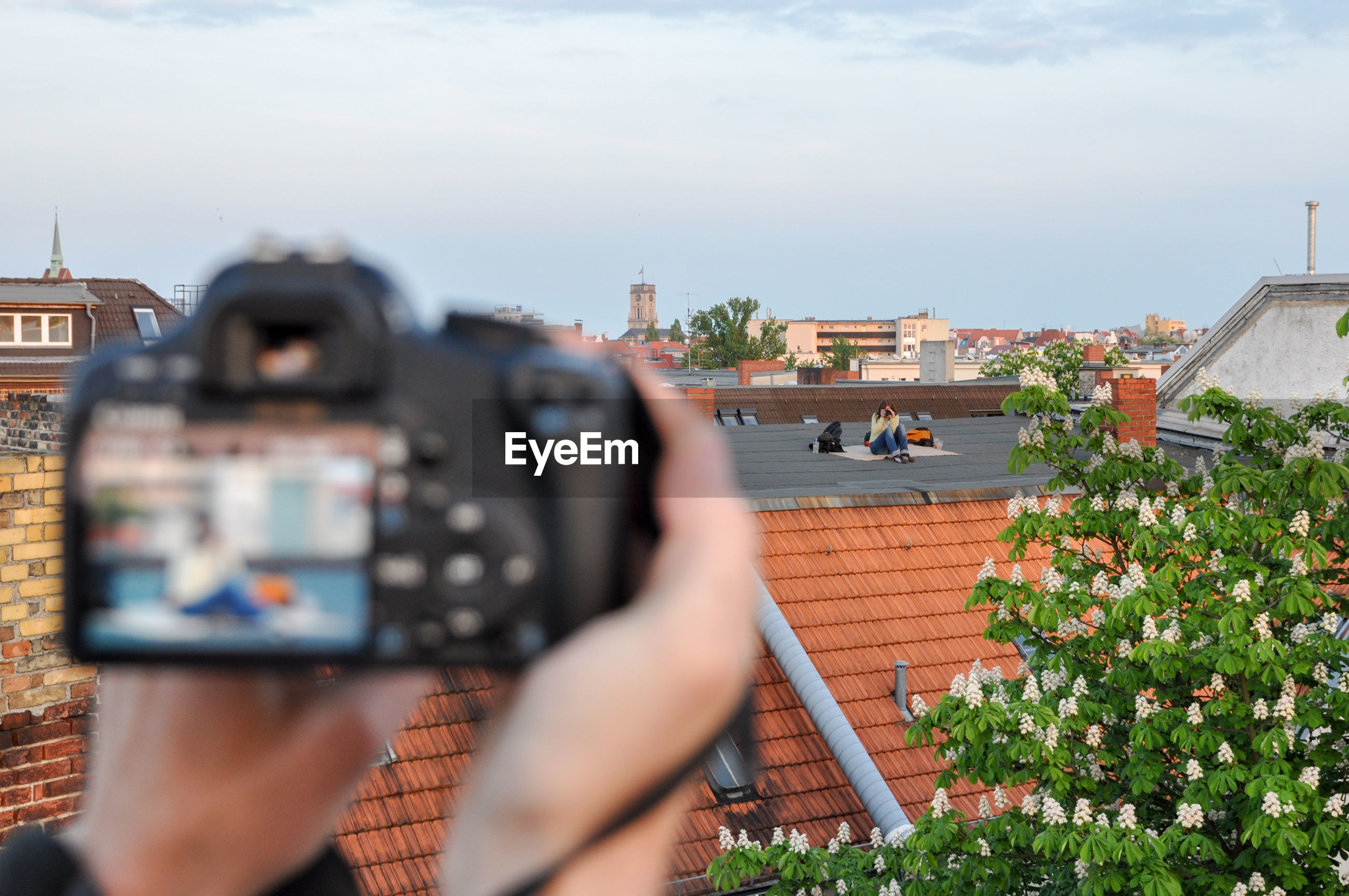Cropped image of person photographing woman sitting on building terrace in city against sky