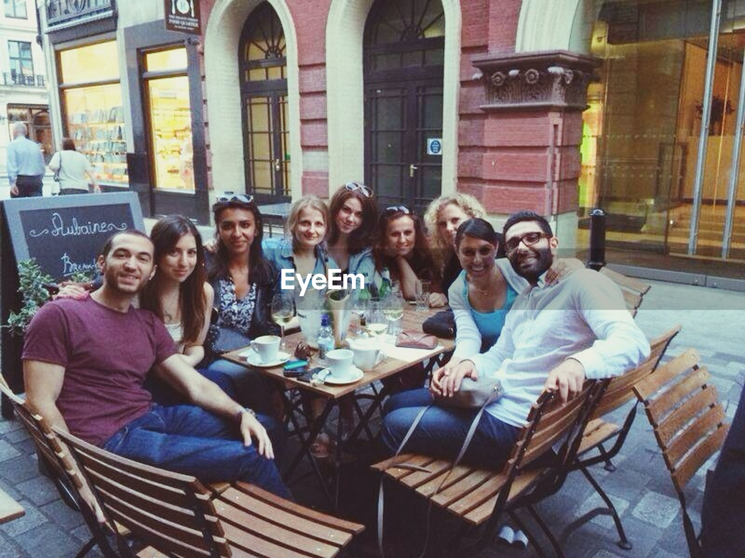 lifestyles, togetherness, leisure activity, casual clothing, person, bonding, young adult, love, friendship, sitting, happiness, building exterior, smiling, architecture, built structure, looking at camera, young women, portrait
