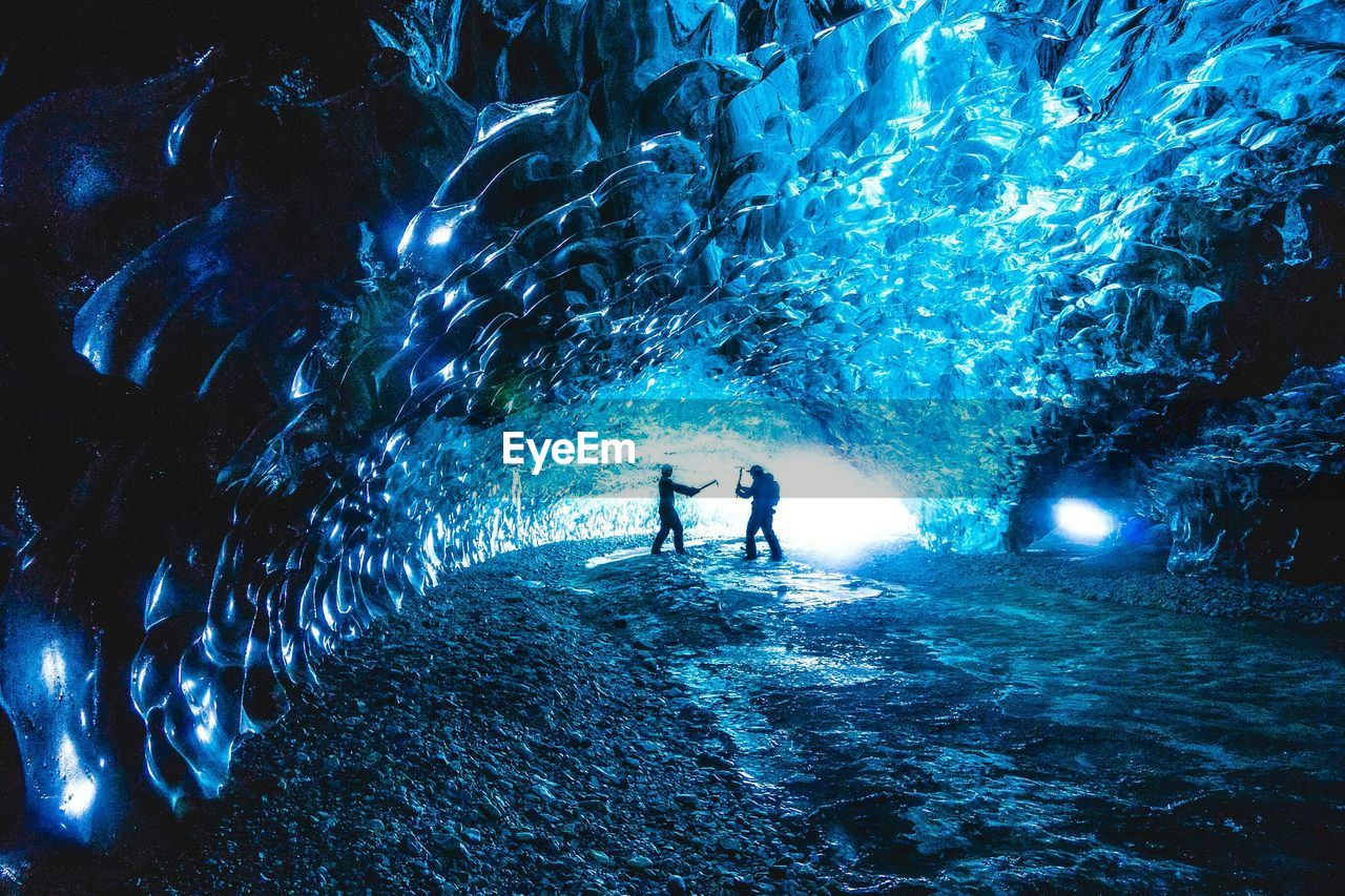 Side view of friends playing inside ice cave