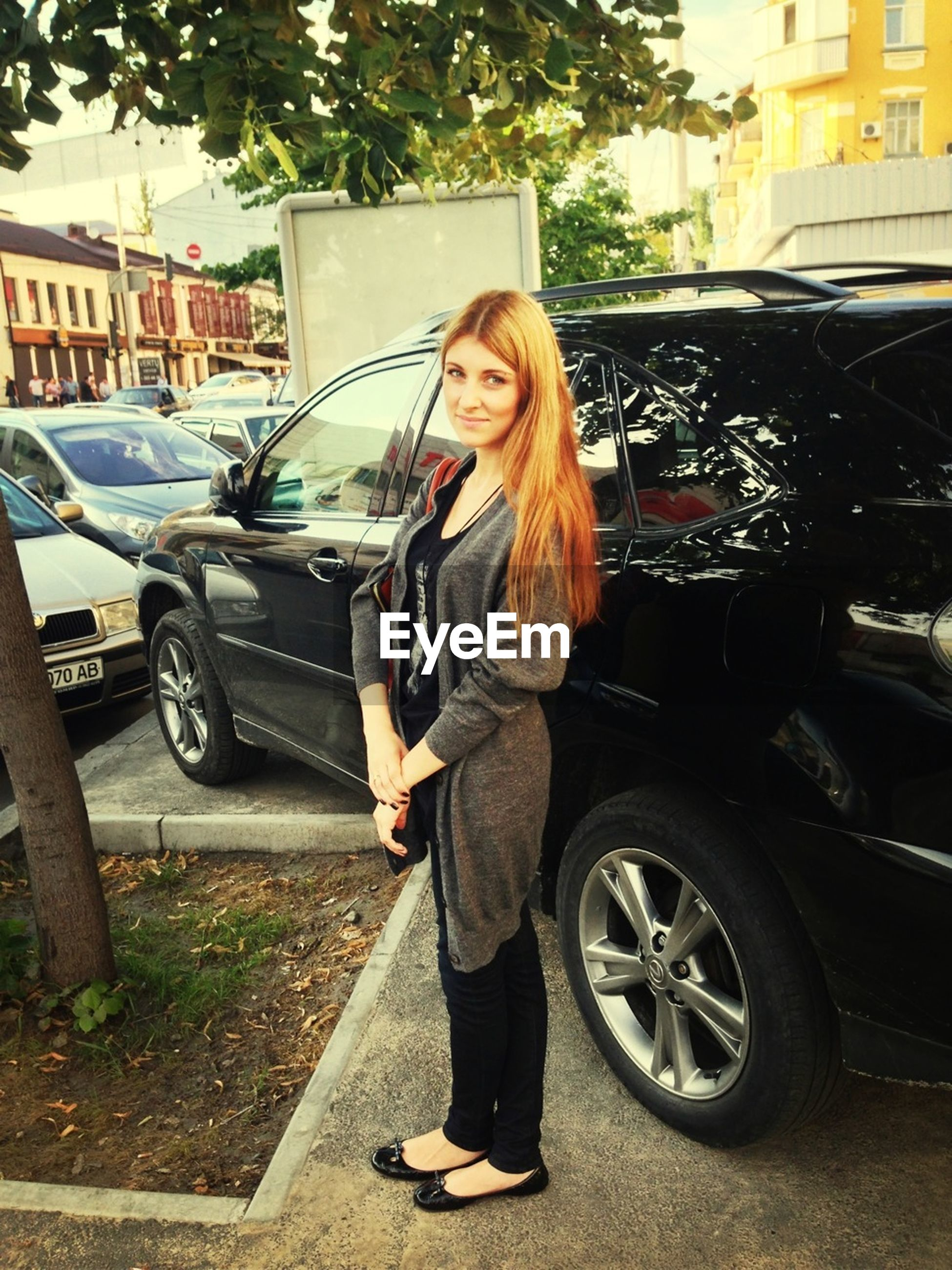 young adult, lifestyles, transportation, mode of transport, person, casual clothing, land vehicle, young women, leisure activity, car, front view, full length, looking at camera, portrait, street, smiling, standing, long hair