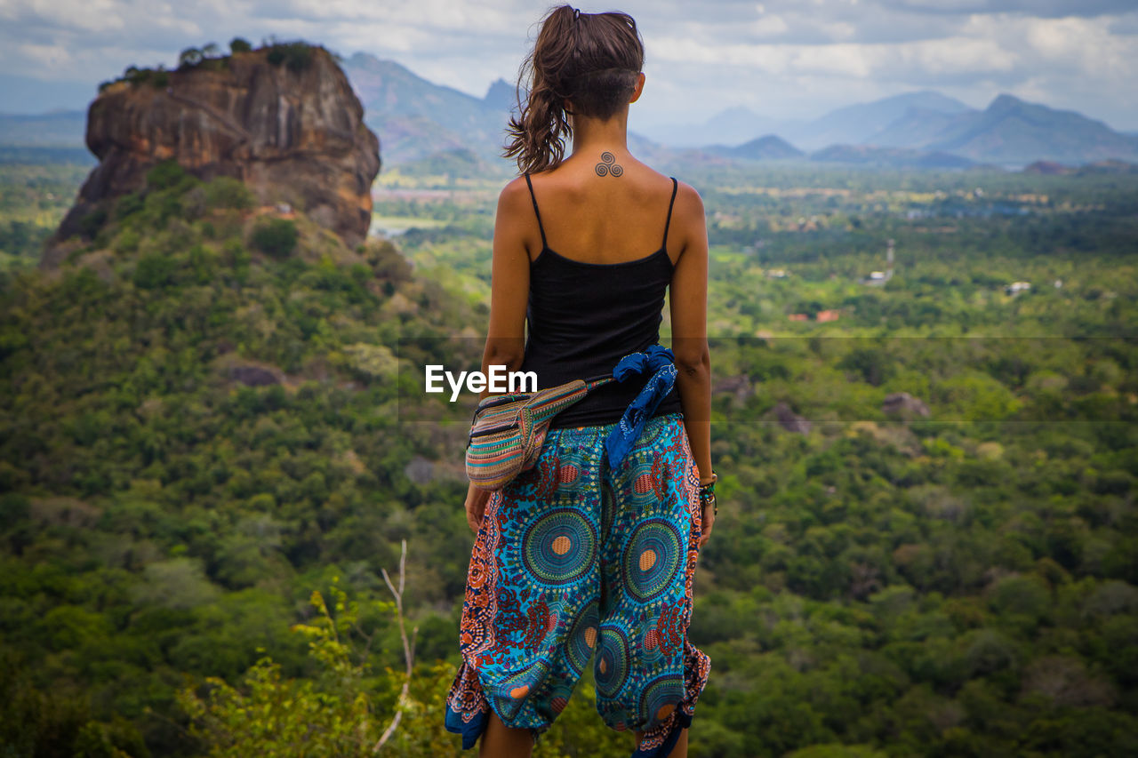one person, real people, lifestyles, rear view, young women, three quarter length, standing, leisure activity, young adult, adult, women, nature, mountain, casual clothing, clothing, beauty in nature, land, day, plant, outdoors, hairstyle