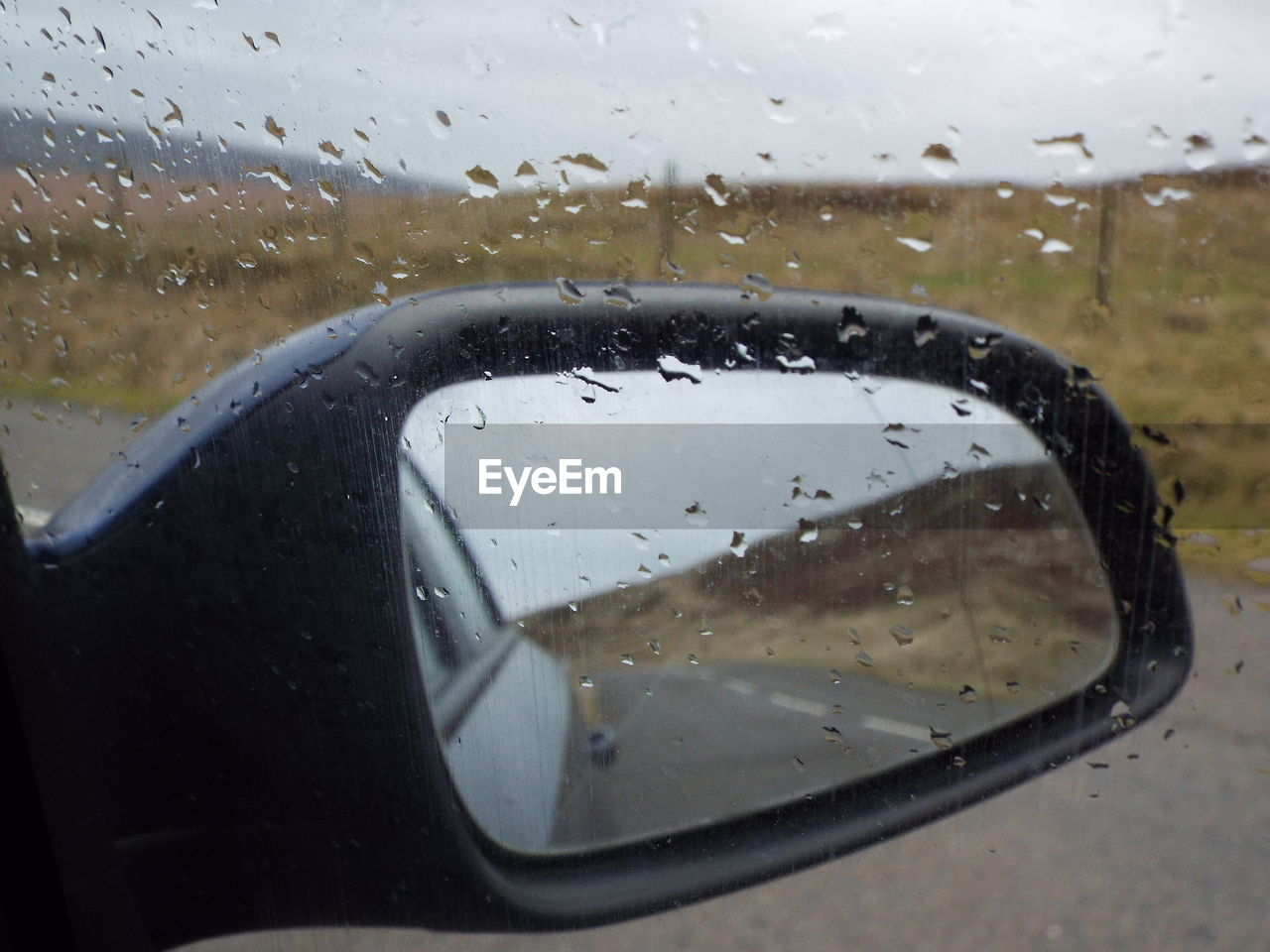 glass - material, wet, drop, transparent, window, rain, water, side-view mirror, vehicle interior, car interior, car, no people, land vehicle, transportation, rainy season, windshield, raindrop, looking through window, close-up, vehicle mirror, mode of transport, reflection, day, road, indoors, nature, sky