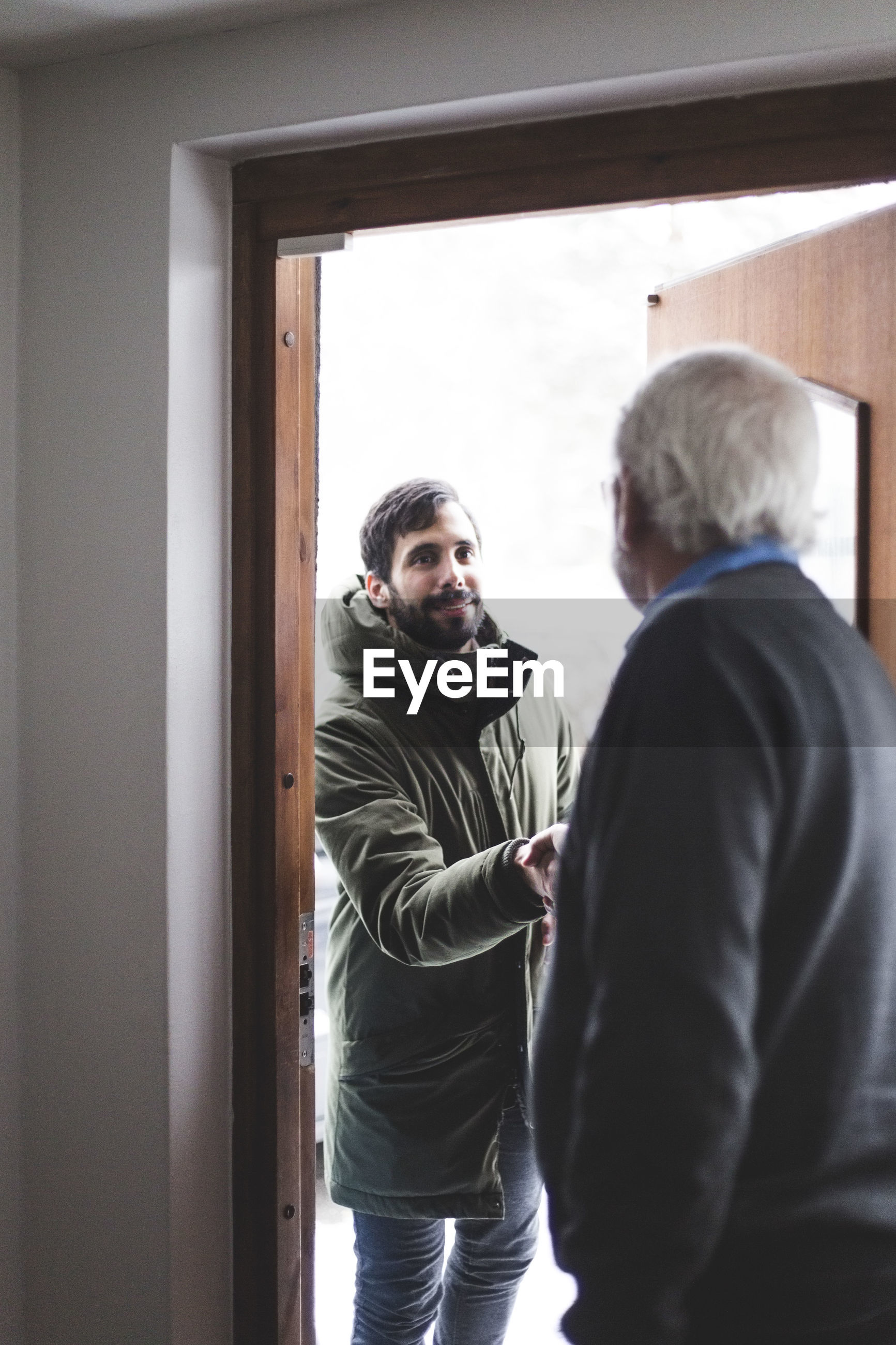 Therapist greeting patient at doorway in home office
