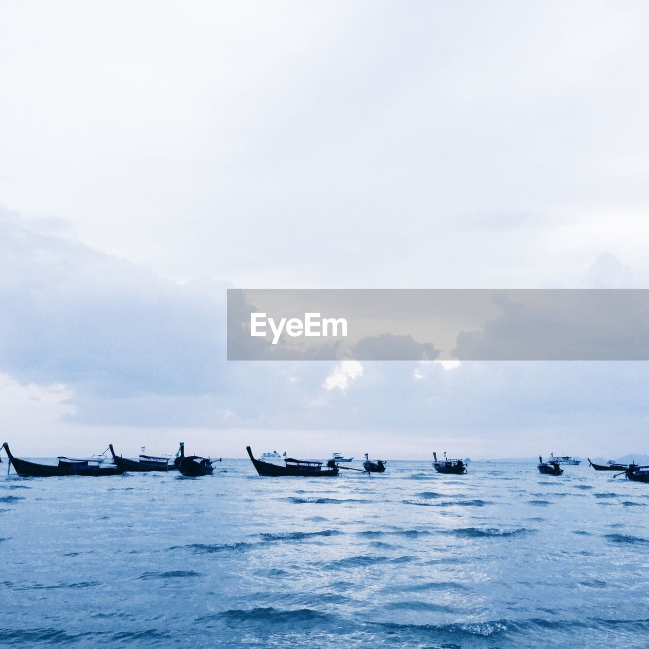 SILHOUETTE BOATS IN SEA AGAINST SKY