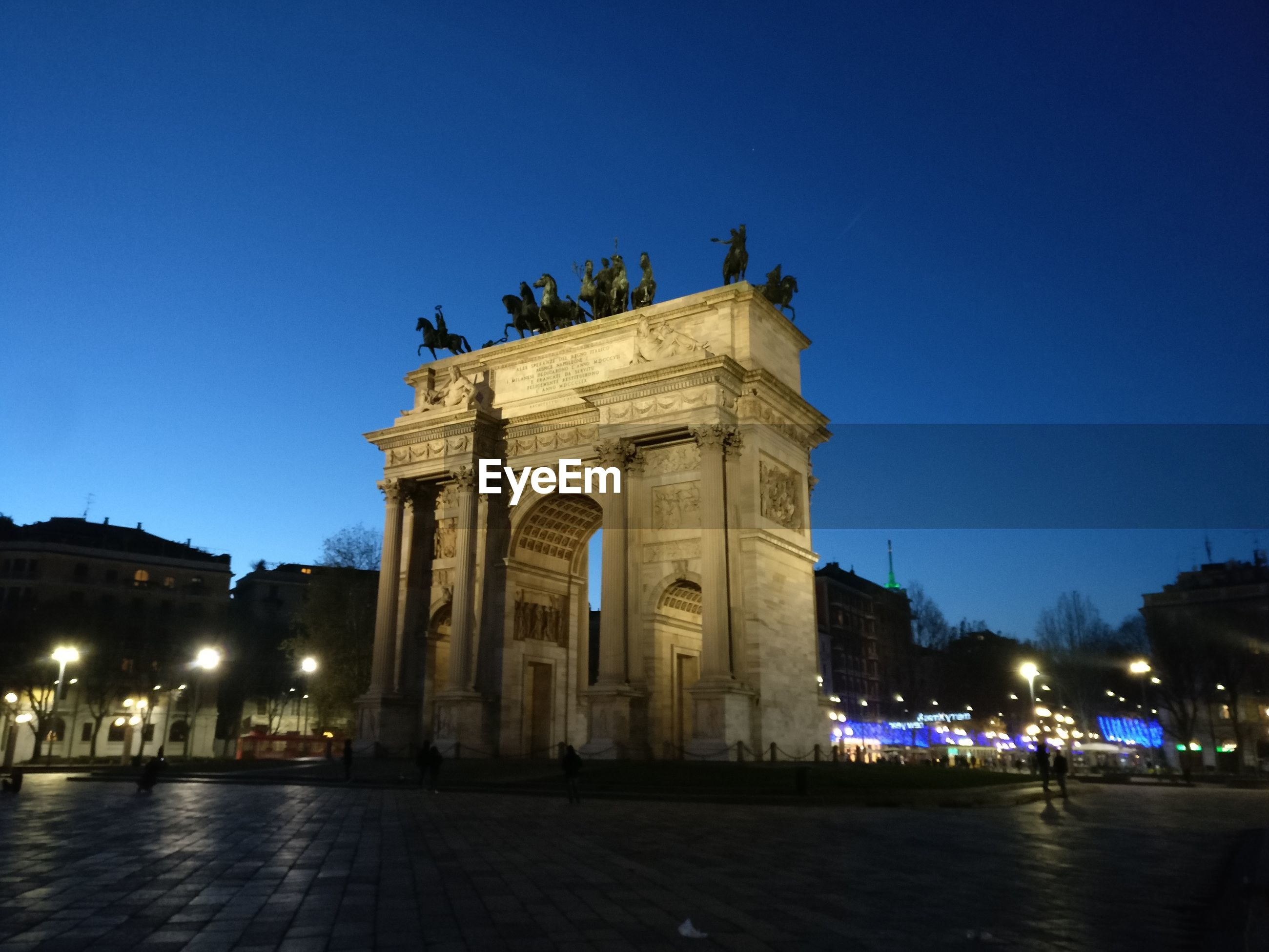 Low angle view of brandenburg gate against clear blue sky at night