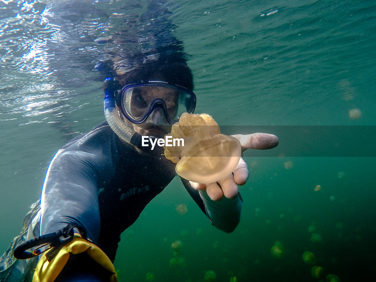 Portrait Of Scuba Diver Holding Jellyfish In Sea