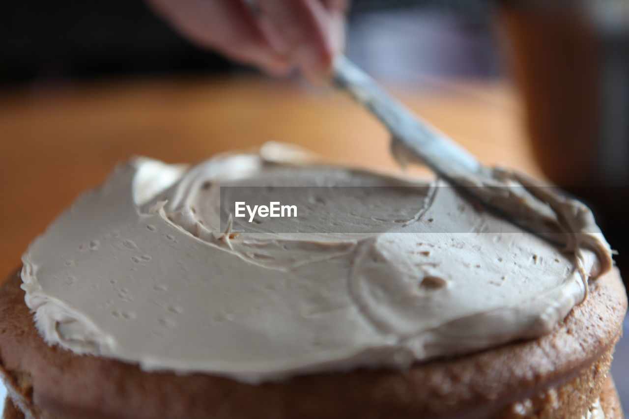 Cropped Hand Spreading Cream On Cake