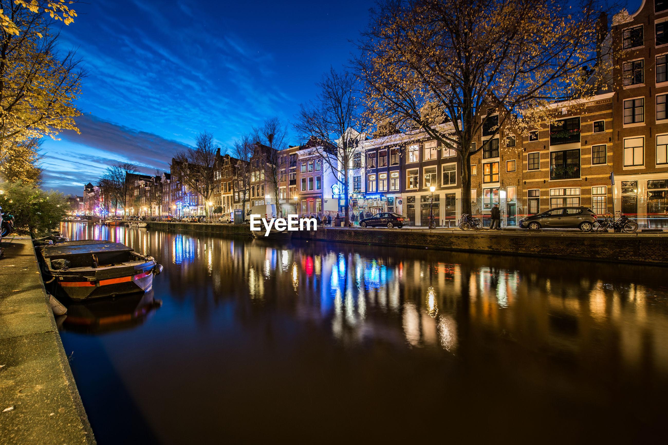 CANAL AMIDST ILLUMINATED CITY AT NIGHT