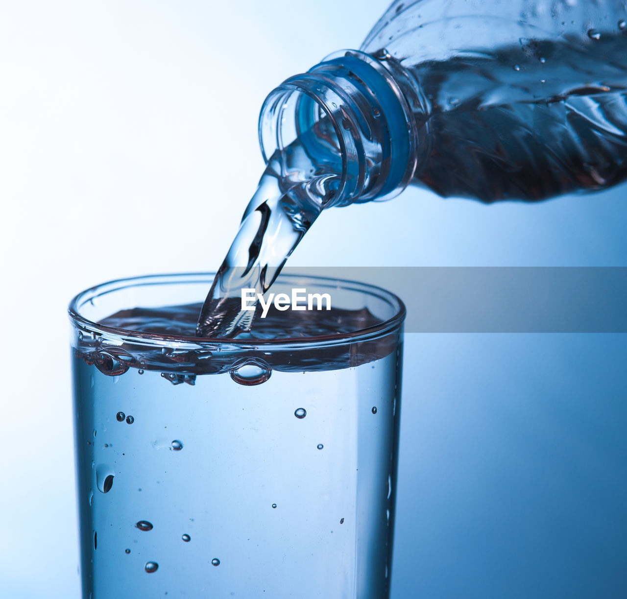 water, drink, refreshment, pouring, motion, glass - material, glass, transparent, drinking glass, studio shot, indoors, close-up, no people, household equipment, blue, food and drink, bottle, container, freshness, purity, flowing, high-speed photography, blue background