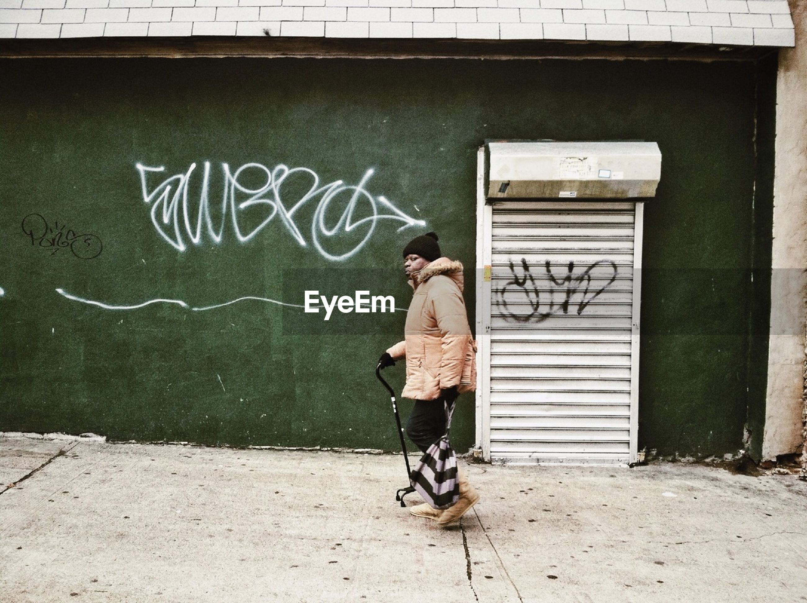 graffiti, wall - building feature, full length, text, built structure, architecture, building exterior, communication, western script, lifestyles, wall, art, day, outdoors, creativity, street art, leisure activity, art and craft