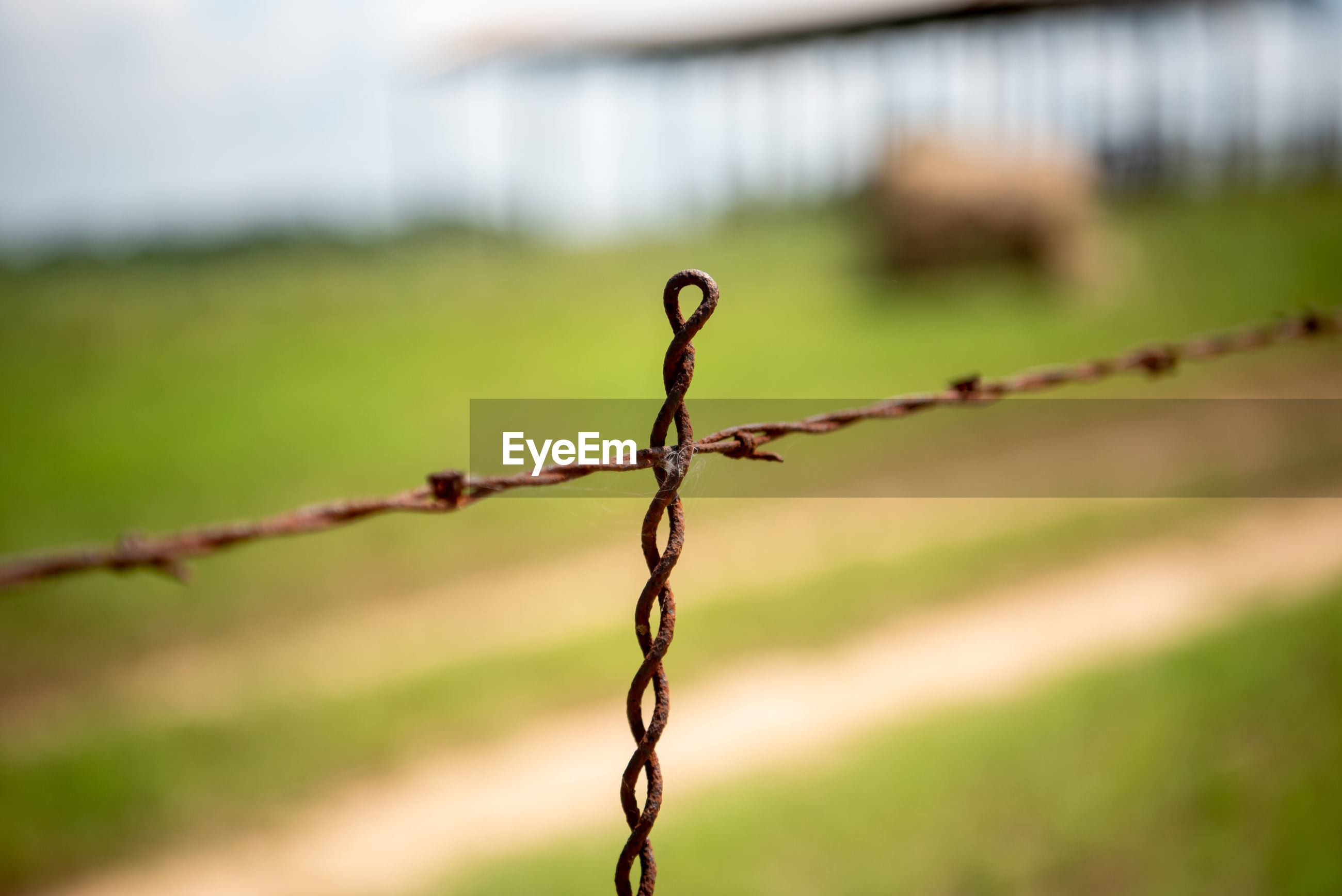 CLOSE-UP OF BARBED WIRE ON METAL FENCE