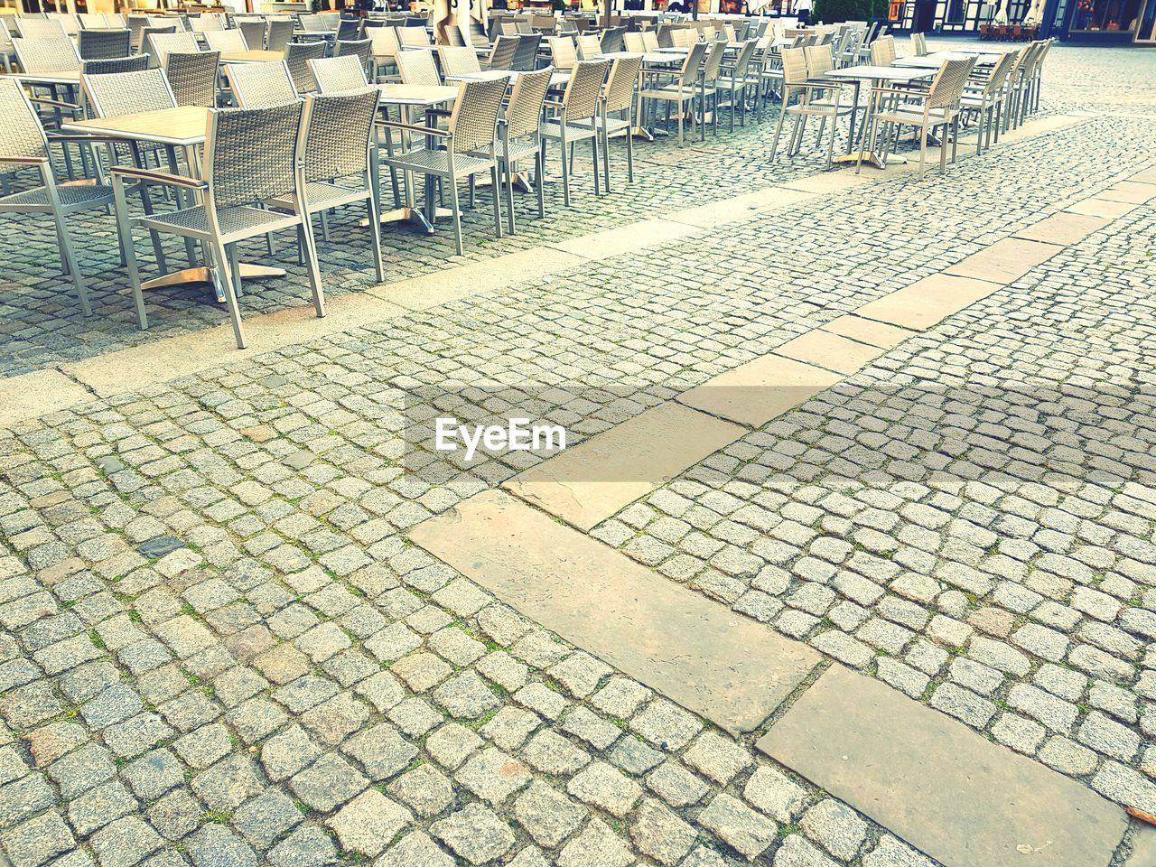 cobblestone, seat, street, stone, paving stone, footpath, chair, no people, city, day, high angle view, absence, architecture, in a row, empty, flooring, outdoors, arrangement, sidewalk, pattern, order, tiled floor