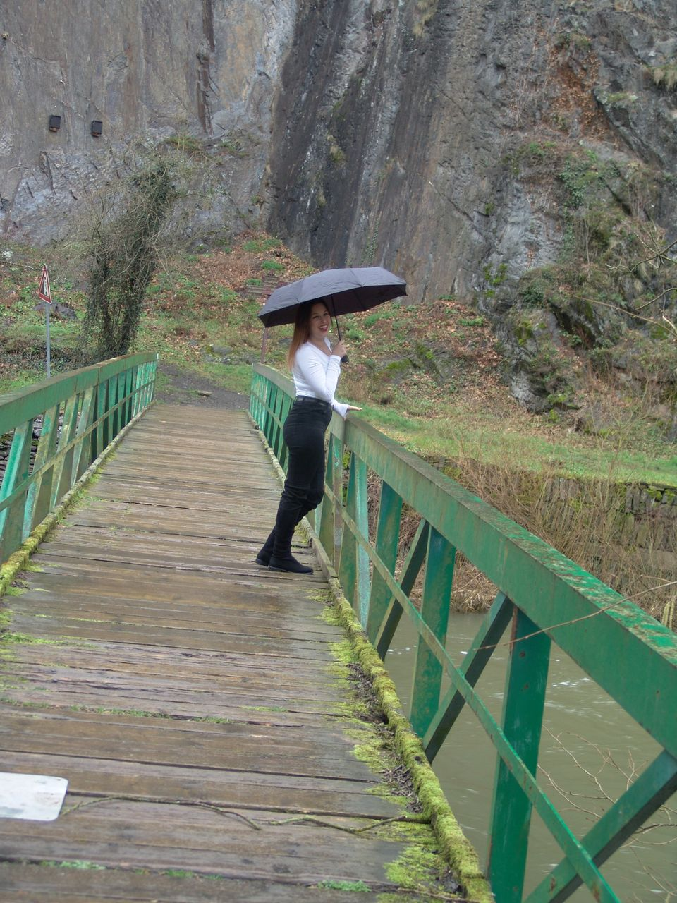 Side View Of Woman Holding Umbrella While Standing On Footbridge Over River