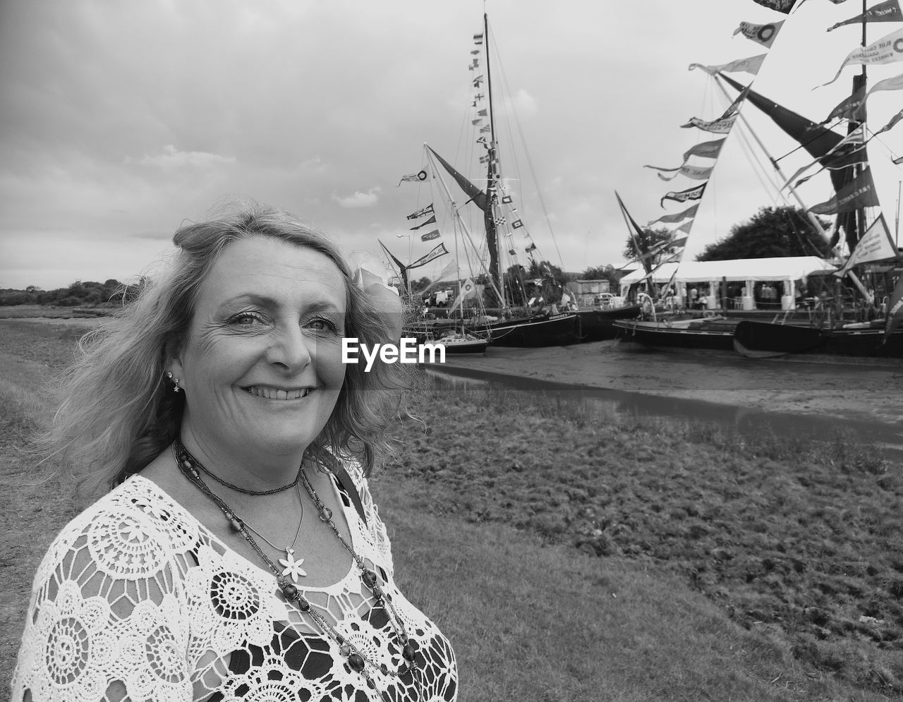 Portrait Of Smiling Mature Woman Standing On Field Against Moored Boats At Harbor